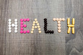 The word health written whith pills on a wooden background. — Fotografia Stock