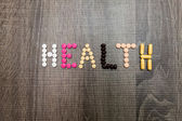 The word health written whith pills on a wooden background. — Stock Photo