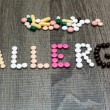 The word allergy written whith pills on a wooden background. — Stock Photo #70940019