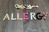 The word allergy written whith pills on a wooden background. — Stock Photo