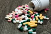 Many colorful pills on a wooden background. — Stock Photo