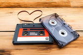 Vintage audio cassette with loose tape shaping two hearts on a w — Stock Photo