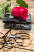 Rose and vintage audio cassette on a wooden background. — Stock Photo