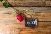Rose and vintage audio cassette with loose tape shaping one hear — Photo