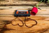 Rose and vintage audio cassette with loose tape shaping two hear — Stock Photo