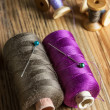 Spools of thread on wooden  background. Old sewing accessories. — Stock Photo #73326527