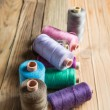 Spools of thread on wooden  background. Old sewing accessories. — Stock Photo #73330417