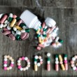 The word doping written with pills on a wooden background. — Stock Photo #73333959