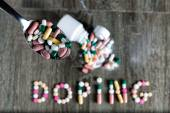 The word doping written with pills on a wooden background. — Stock Photo