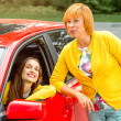 Mother with her daughter near red car — Stock Photo #56988363
