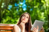 Young woman with digital tablet in the park — Stock Photo