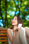 Young woman with mobile phone in the park — Stok fotoğraf