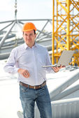 A foreman with laptop at the construction supervising the project. — Stock Photo