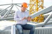A foreman with digital tablet at the construction supervising the project. — Stock Photo