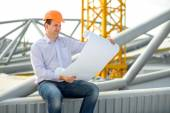 A foreman with drawings supervising the project at the construction. — Stock Photo