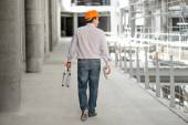 A foreman with drawings and case supervising the project at the construction. — Stock Photo
