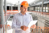 A foreman with digital tablet supervising the project at the construction. — Stock Photo