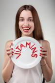 Young woman showing plate with vitamins — Stock Photo
