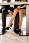 Legs of a couple sitting at the restaurant — Stock Photo