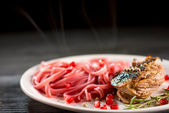 Pasta with steak on wooden table — Stock Photo