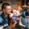 Young couple with gift boxes at the cafe in winter — Stock Photo #59285127