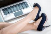 Woman legs and laptop — Стоковое фото