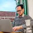 Man with laptop on the balcony — Stock Photo #66852595