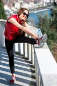 Sporty woman on the park alley with city view — Stock Photo