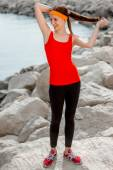 Sport woman on the rocky beach — Stock Photo