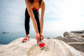 Sporty woman legs on the rocky beach — Stock Photo