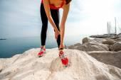 Sporty woman legs on the rocky beach — Stock Photo