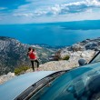 Woman photographer with car on the top of mountain — Stock Photo #68566173
