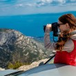 Woman photographer with car on the top of mountain — Stock Photo #68567045