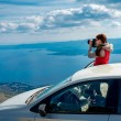 Woman photographer with car on the top of mountain — Stock Photo #68567533