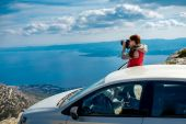 Woman photographer with car on the top of mountain — Stock Photo