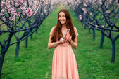 Woman enjoying spring in the green field with blooming trees — Foto de Stock