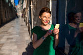 Woman with mobile phone in old city street — Stock fotografie