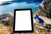 Digital tablet with sunglasses on the mountain — Stock Photo