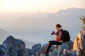 Young photographer on the top of mountain — Stock Photo