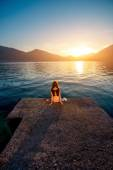 Woman sitting on the pier at sunrise — Stock Photo