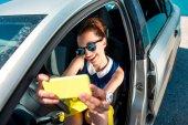 Mulher fazendo auto-retrato no carro — Fotografia Stock