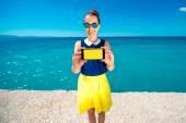 Woman showing phone screen near the sea — Stock Photo
