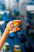 Holding colorful coffee cup on blured city background — Стоковое фото