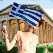 Woman with Greek flag on Hephaistos temple background — Stock Photo #72980555