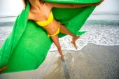 Woman in green towel on the beach — Stock Photo