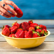 Taking strawberry from the yellow plate — Stock Photo #73369673