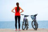 Sport woman with bicycles on the beach — Stock Photo