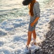 Woman in stripped dress with a hat on the beach — Stock Photo #76604327