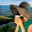 Woman with coffee cup in the mountains — Stock Photo #76689893