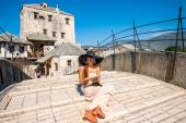 Woman sitting on the old bridge in Mostar city — Stock Photo
